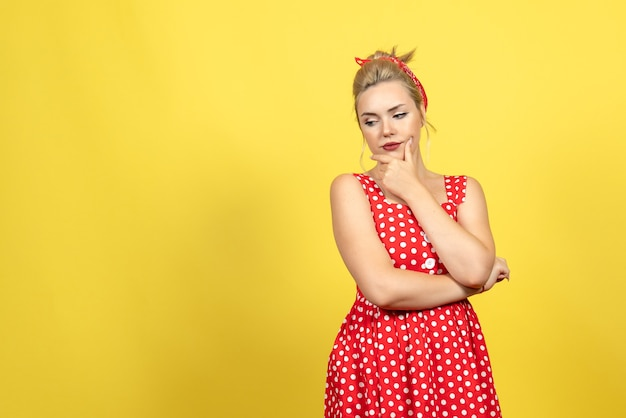 Young female in red polka dot dress thinking on yellow