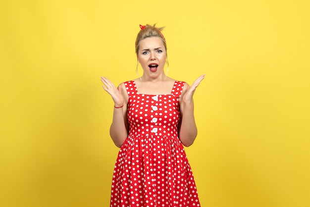 Young female in red polka dot dress on yellow