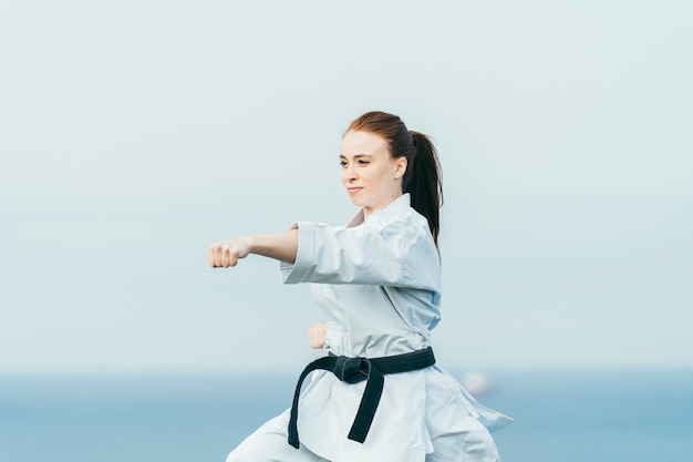 Young female redhead karate fighter hitting a left punch