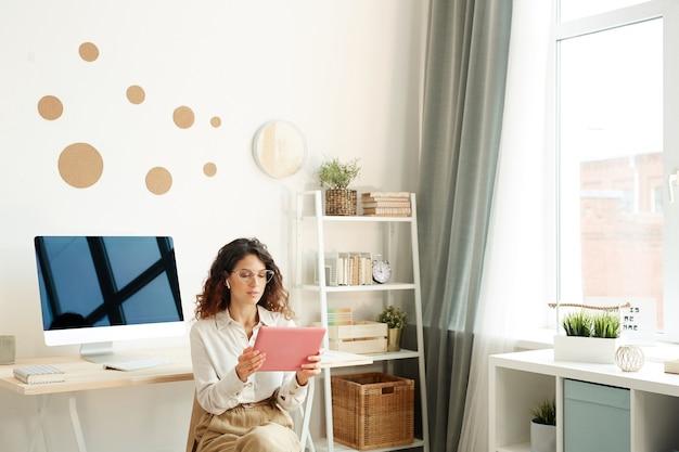 タブレットコンピューターを使用してオンライン会議に参加している彼女の部屋の椅子に座っている若い女性のリモートワーカー
