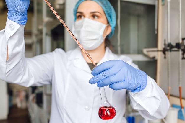 의료 모자와 보호 마스크의 젊은 여성 연구원이 테스트 튜브로 조사를하고 있습니다.