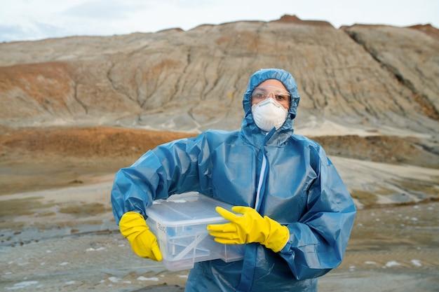 Молодая женщина-исследователь в защитном комбинезоне, респираторе, резиновых перчатках и очках держит пластиковый контейнер с образцами воды и почвы