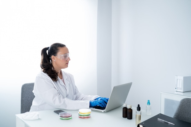 Young female researcher or scientist in white coat and blue gloves is writing on a laptop in a laboratory