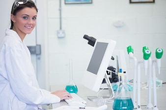 Young female researcher using computer in lab