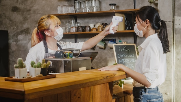 Young female restaurant staff wearing protective face mask using infrared thermometer checker or temperature gun on customer's forehead before enter.