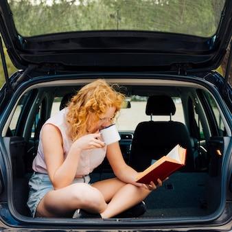 자동차의 트렁크에 앉아있는 동안 휴식하는 젊은 여성