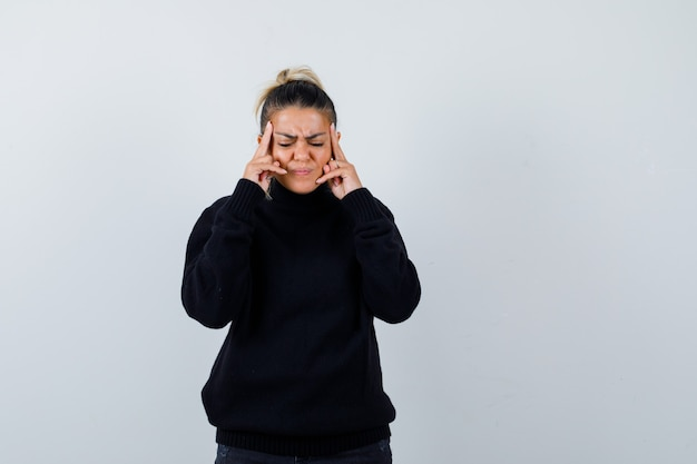 Young female rubbing temples in black turtleneck sweater and looking fatigued. front view.