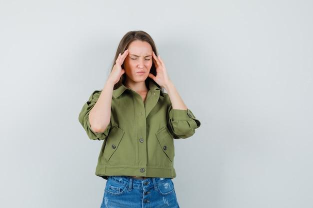 재킷, 반바지에 두통이 있고 피곤한 정면보기로 인해 사원을 문지르는 젊은 여성.