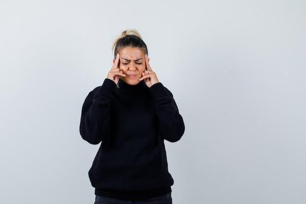 黒のタートルネックのセーターで寺院をこすり、疲れているように見える若い女性。正面図。