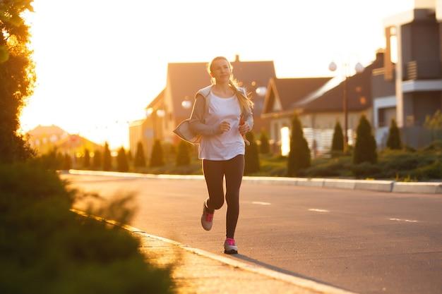 若い女性ランナー、アスリートは日差しの中で街の通りでジョギングしています。音楽を聴いて、美しい白人女性のトレーニング