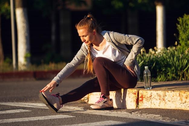 若い女性ランナー、アスリートは日差しの中で街の通りでジョギングしています。