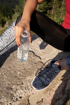 水のボトルを保持している若い女性ランナー