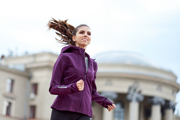 Young female runner in hoody is jogging in city street