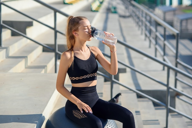 Young female runner is having break, drinking water during the run outdoor in city