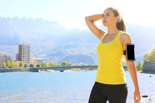 空白のスマートフォンアームバンドを身に着けている若い女性ランナー