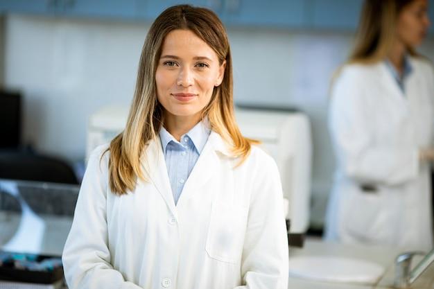 생물 의학 실험실에 서있는 흰색 실험실 코트에 젊은 여성 과학자
