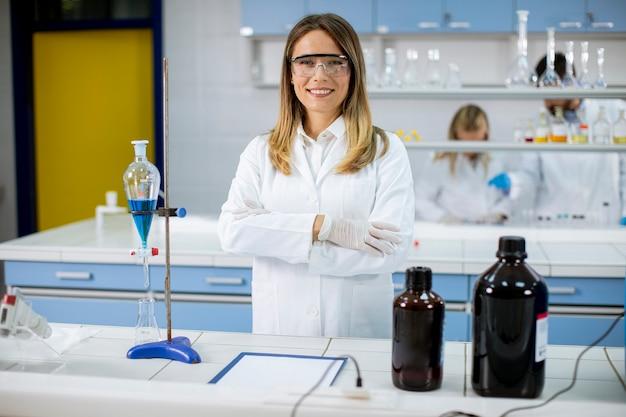 Молодая женщина-ученый в белом лабораторном халате стоит в биомедицинской лаборатории
