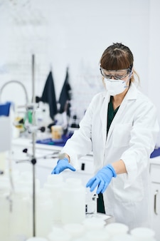 Young female scientist in lab coat, goggles, gloves and safety mask working in a lab