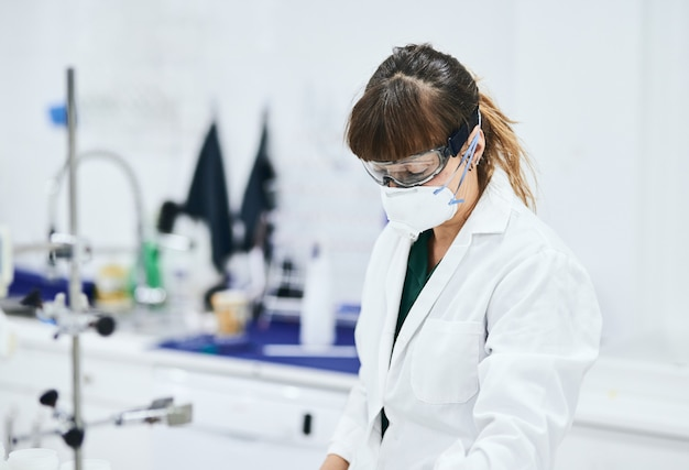 Young female scientist in lab coat, goggles and safety mask working in a lab
