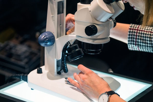 실험실에서 현미경을 통해 찾고 젊은 여성 과학자.