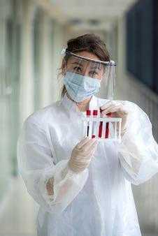 임상 실험실에서 혈액 샘플을 연구하는 젊은 여성 과학자. 코로나 바이러스 또는 covid-19 개념