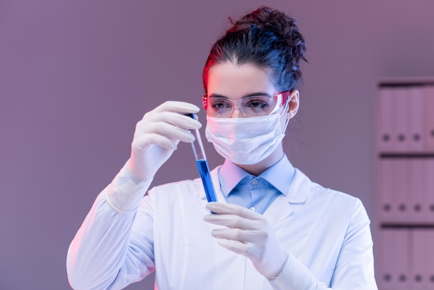 Young female scientist in mask, gloves and eyeglasses looking at flask while studying blue liquid substance in laboratory