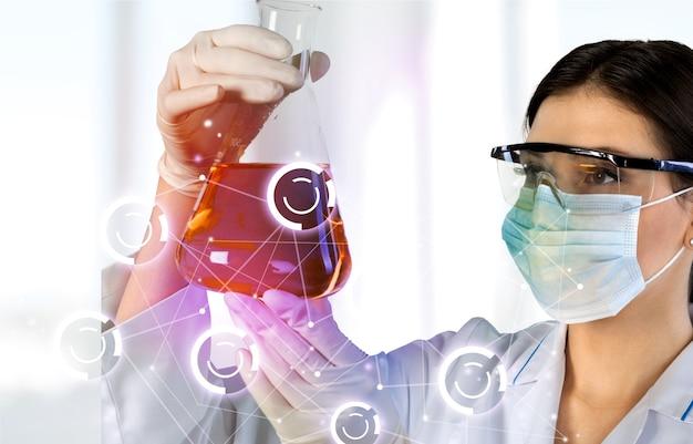 Молодая женщина-ученый, стоя в своей лаборатории.