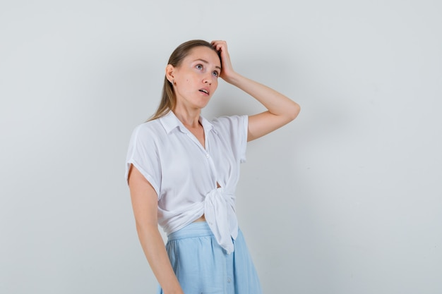 Giovane donna grattandosi la testa in camicetta e gonna e guardando pensieroso