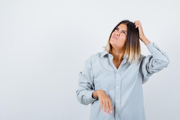 Giovane femmina che graffia la testa in una camicia sovradimensionata e sembra premurosa. vista frontale.