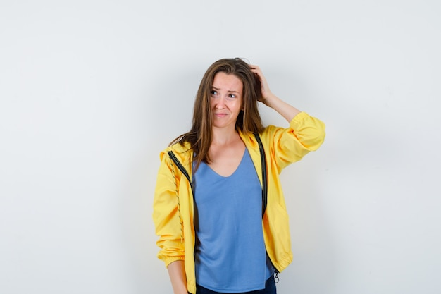 Giovane femmina che graffia la testa in maglietta, giacca e sembra pensierosa, vista frontale.