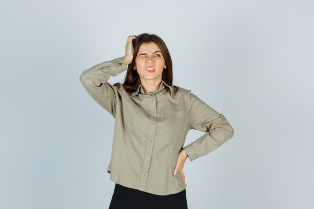 Young female scratching head while frowning in shirt and looking forgetful