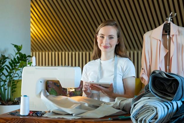 젊은 여성 재봉사가 바느질 작업장에서 노트북의 의류 측정에 대해 메모합니다.
