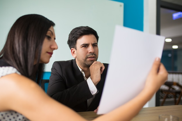 Young female secretary showing document to puzzled executive