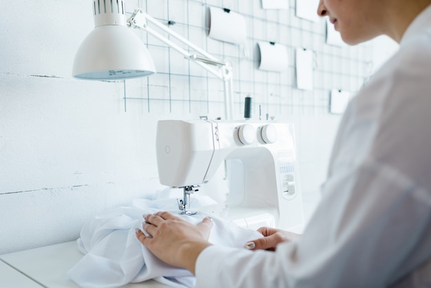 Young female sewing factory worker in white workwear sitting by electric machine while creating new clothes