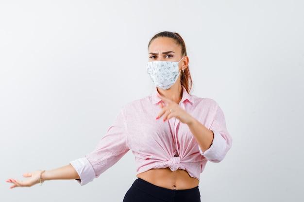 Giovane donna in camicia, pantaloni, mascherina medica che punta lontano e guardando fiducioso, vista frontale.