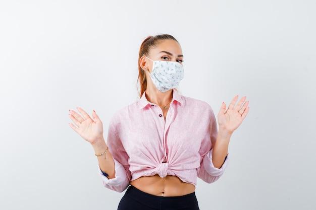 Giovane donna in camicia, pantaloni, maschera medica che mostra i palmi in gesto di resa e sembra impotente, vista frontale.
