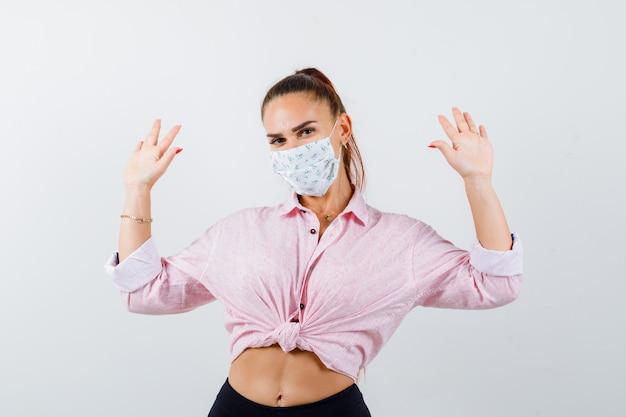 Giovane femmina in camicia, pantaloni, mascherina medica che mostra i palmi in gesto di resa e che sembra seria, vista frontale.