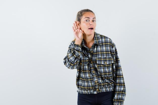Giovane donna in maglietta, pantaloncini tenendo la mano dietro l'orecchio e guardando curioso, vista frontale.