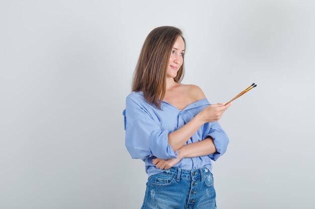 Giovane donna in camicia, pantaloncini tenendo i pennelli e guardando allegro