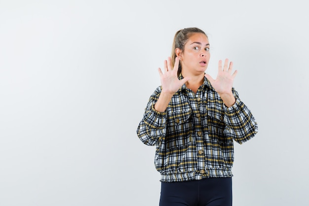 Young female in shirt, shorts showing stop gesture and looking scared , front view.