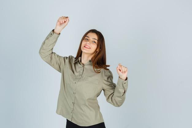 Giovane femmina in camicia che mostra il gesto del vincitore e che sembra fortunato