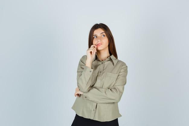 Giovane donna in camicia, gonna che tiene la mano sul mento mentre guarda in alto e sembra pensierosa, vista frontale.