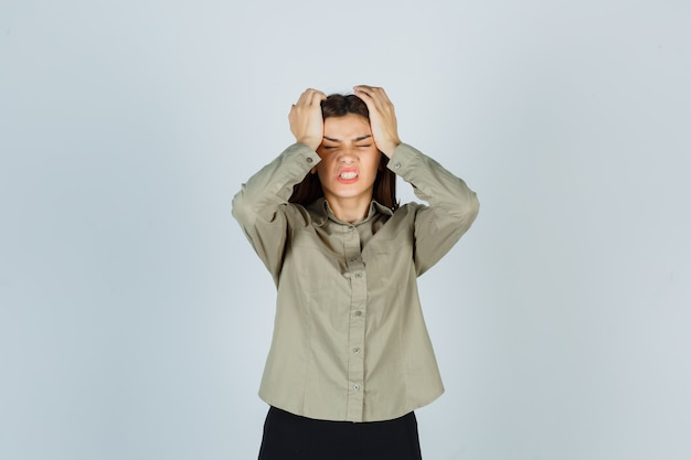 Giovane donna in camicia, gonna che tiene le mani sulla testa e sembra infastidita, vista frontale.
