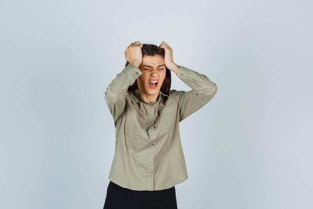 Giovane donna in camicia, gonna che tiene le mani sulla testa mentre urla e sembra triste, vista frontale.
