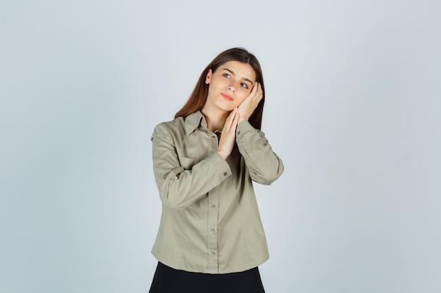 Giovane donna in camicia, gonna appoggiata sul palmo come cuscino e guardando premurosa, vista frontale.