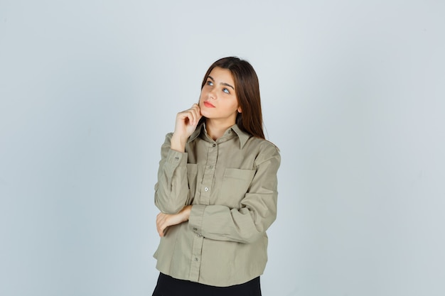 Giovane donna in camicia, gonna appoggiando il mento a portata di mano e guardando pensieroso