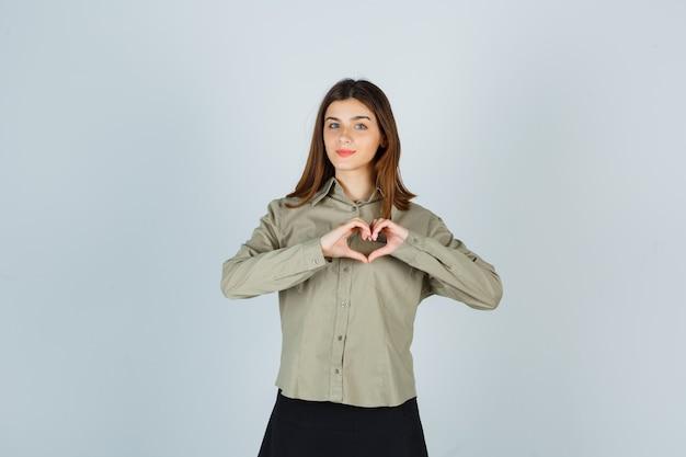 Giovane femmina in camicia, gonna che mostra il gesto del cuore e che sembra sicura