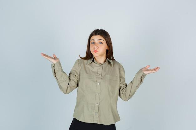 Giovane donna in camicia, gonna che mostra gesto impotente, guance che soffia