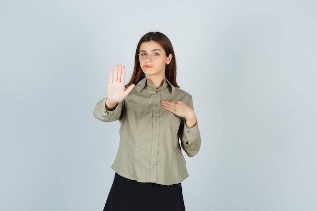 Giovane donna in camicia, gonna che mostra il gesto di rifiuto, tenendo la mano sul petto