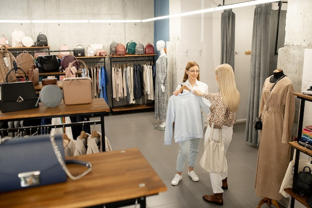 Young female shop assistant showing white sweatshirt from new fashion collection to blond elegant woman standing in front of her in boutique